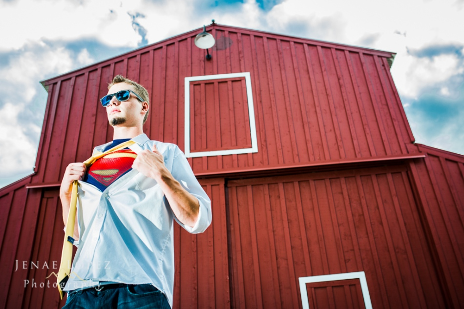 creative Denver senior photo with guy holding shirt open to reveal Superman shirt standing in front of Red Barn